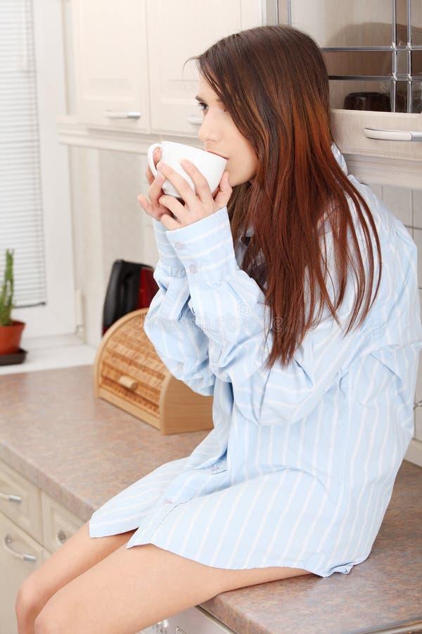 Jeune femme ayant le café de matin image stock