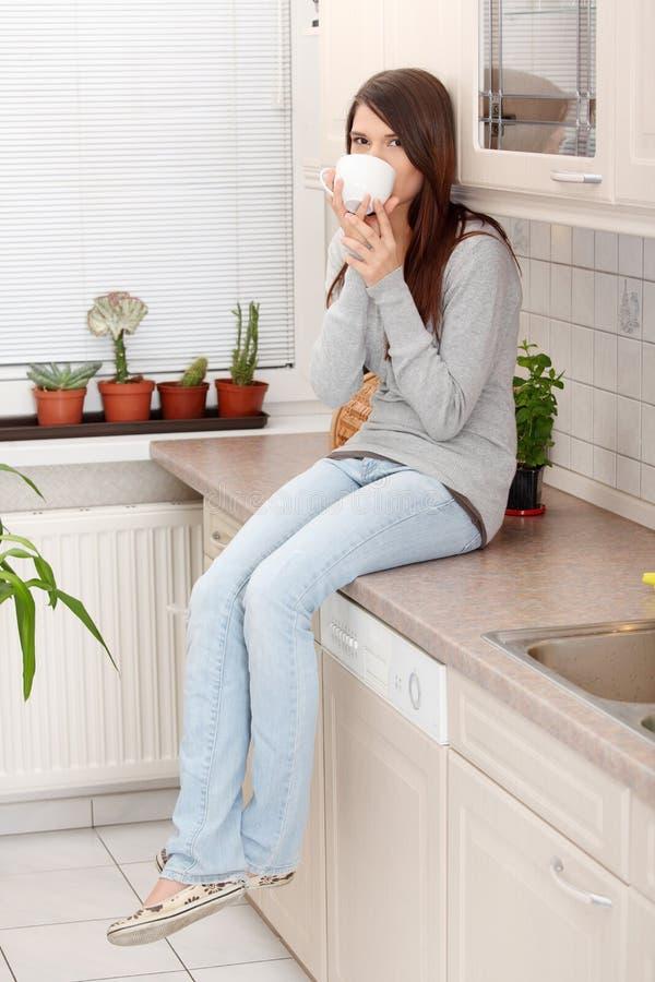 Jeune femme ayant le café ou le thé dans la cuisine images stock