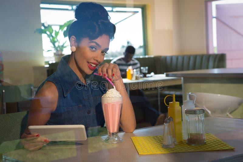 Jeune femme ayant le milkshake et tenant le comprimé regardant dans l'appareil-photo photos libres de droits