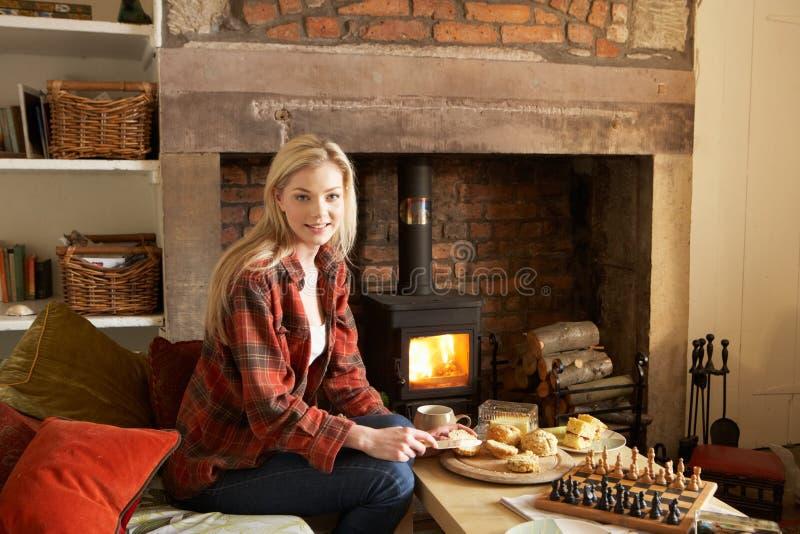 Jeune femme ayant le thé par l'incendie photo libre de droits
