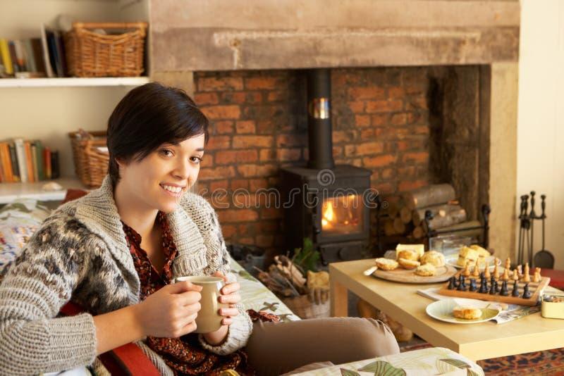 Jeune femme ayant le thé par l'incendie photographie stock