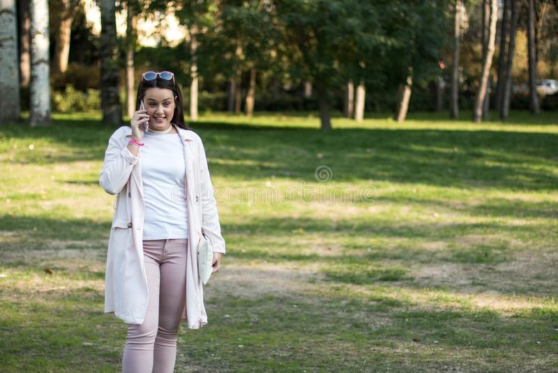 Jeune femme ayant une conversation sur son smartphone photo libre de droits