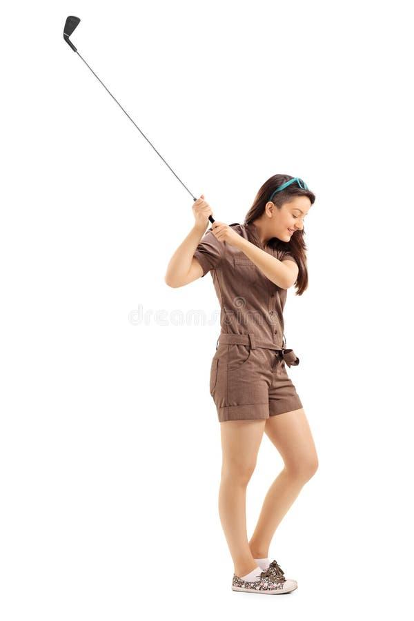 Jeune femme balançant un club de golf photographie stock