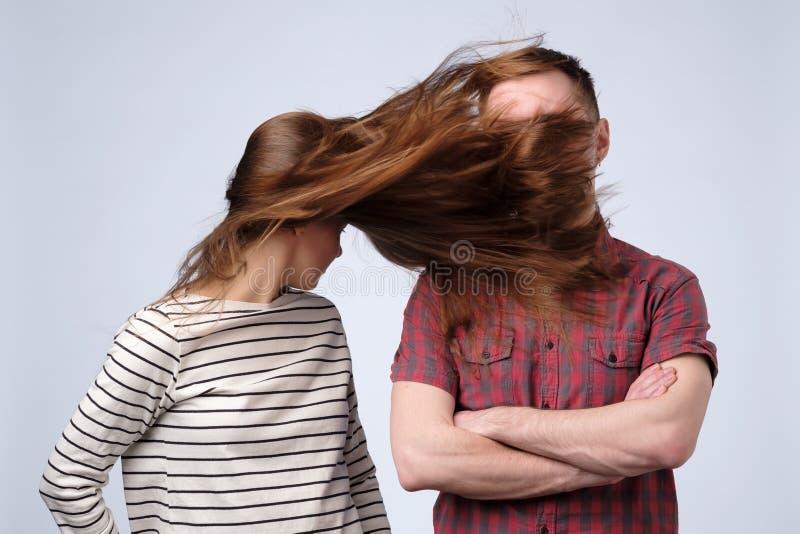 Jeune femme battant son mari avec de longs cheveux image stock