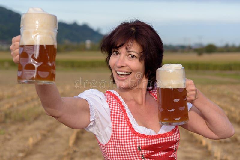Jeune femme bavaroise heureuse célébrant Oktoberfest photos libres de droits