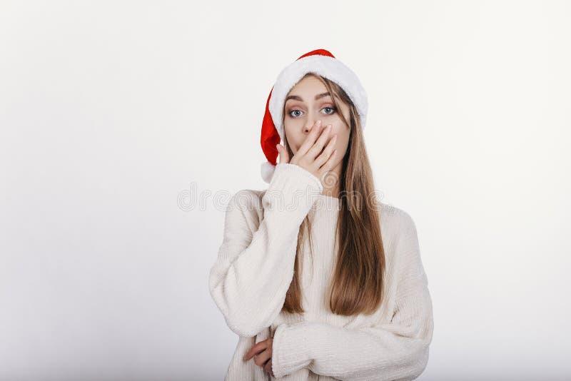 Jeune femme blanche caucasienne dans le chapeau de Santa couvrant sa bouche à la main image stock