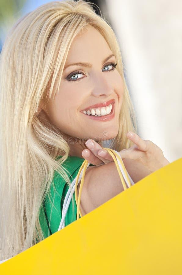 Jeune femme blond avec des œil bleu et des sacs à provisions photographie stock libre de droits