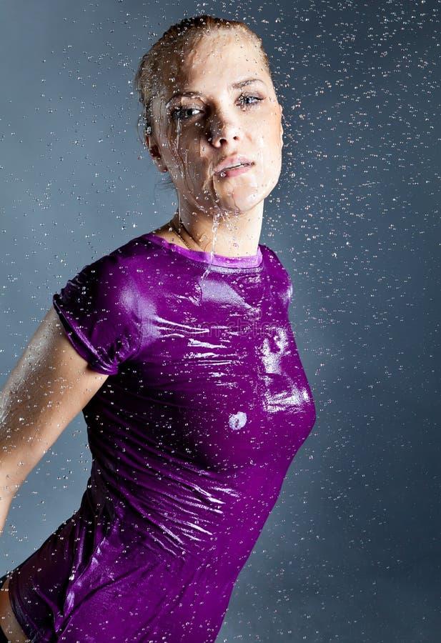 Jeune femme blond dans des gouttelettes d'eau photographie stock