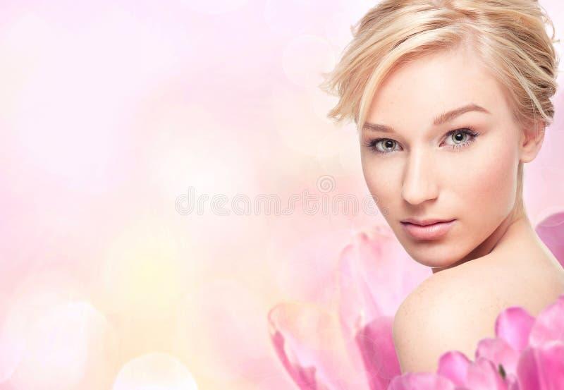 Jeune femme blond dans des pétales de fleur photo stock