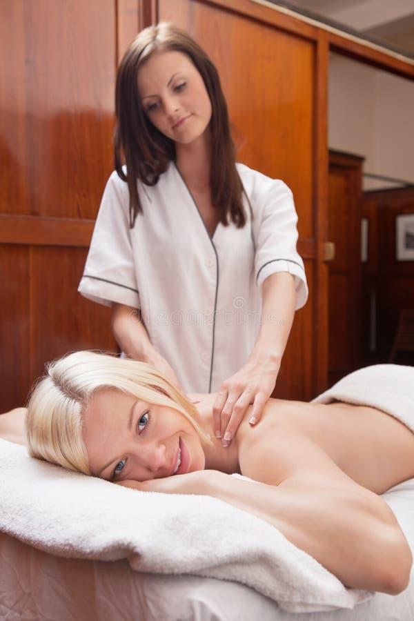 Jeune femme blond recevant le massage image stock