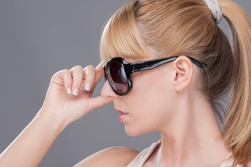 Jeune femme blond retenant le sunglasse moderne photographie stock libre de droits