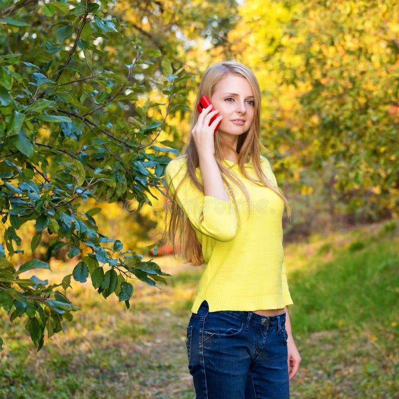 Jeune femme blonde à l'aide d'un téléphone portable marchant dans le parc d'automne photographie stock