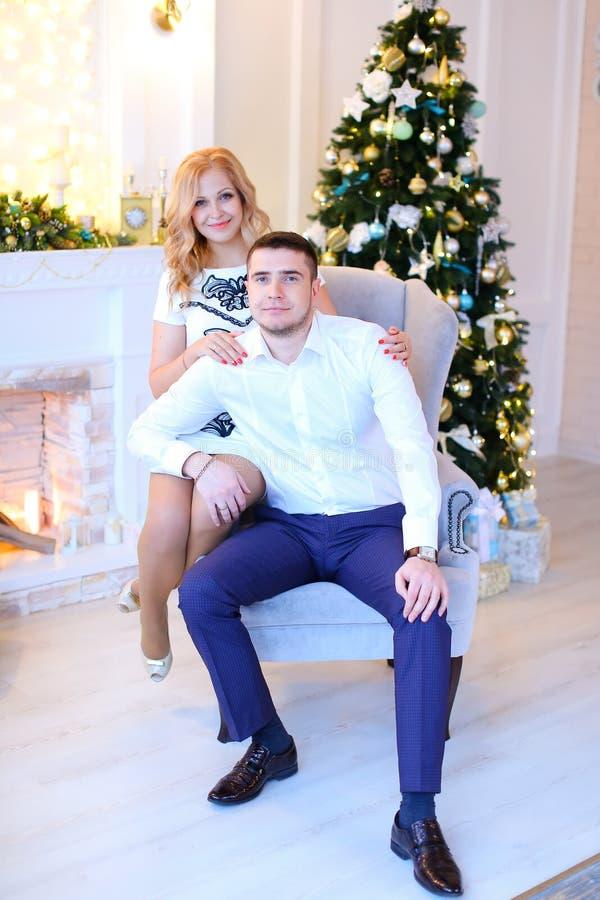 Jeune femme blonde étreignant le mari près de l'arbre de Noël photo libre de droits