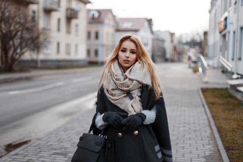 Jeune femme blonde attirante à la mode dans un chandail tricoté par cru dans un manteau élégant dans les gants chauds avec une éc photo stock