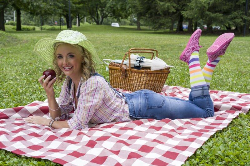 Jeune femme blonde attirante posant dehors pendant le pique-nique images libres de droits
