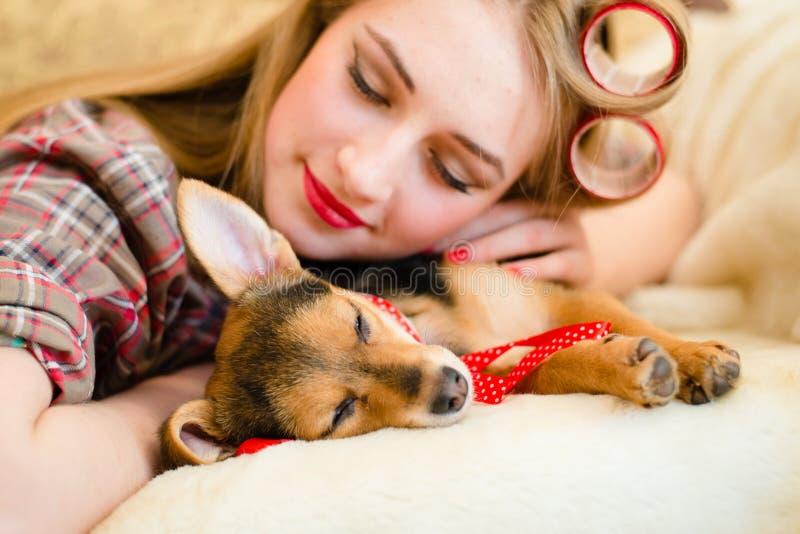 Jeune femme blonde avec des bigoudis dormant avec son petit chiot image stock