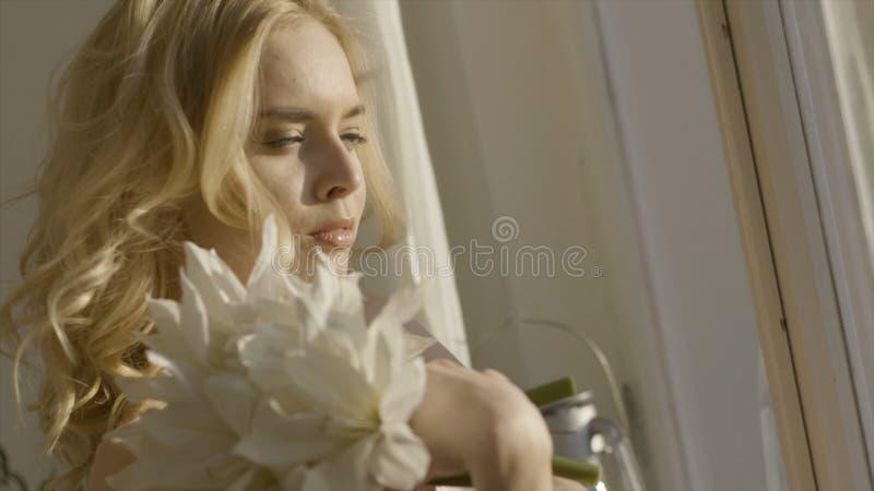 Jeune femme blonde avec des fleurs dans des ses mains au soleil action Jeune belle femme au soleil à la maison avec des fleurs photos libres de droits