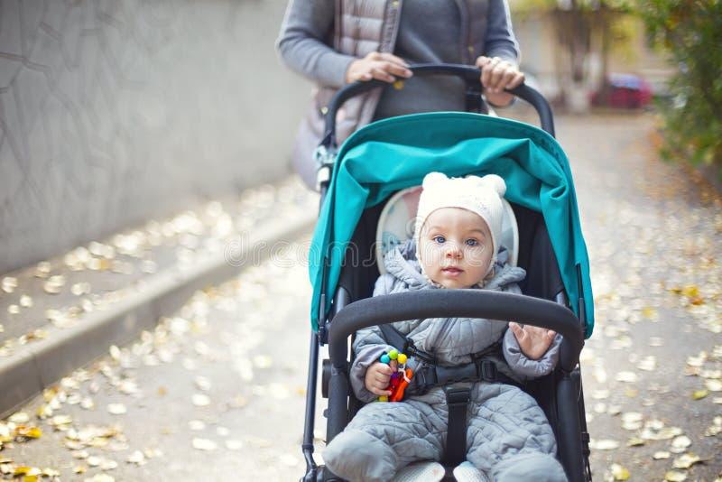 Jeune femme blonde avec la poussette faisant une promenade en parc photos libres de droits