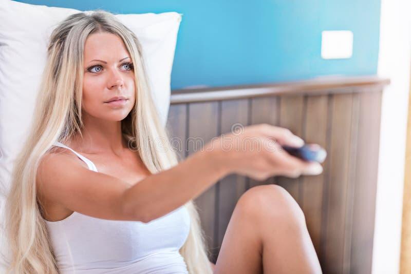 Jeune femme blonde avec la TV ? t?l?commande dans le lit image libre de droits