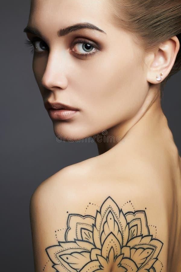 Jeune femme blonde avec le tatouage photo libre de droits