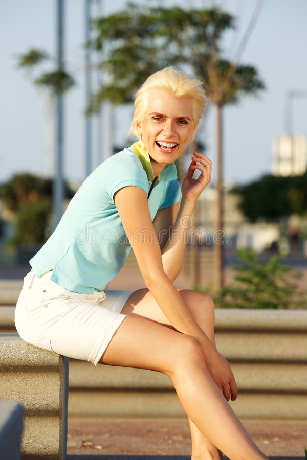 Jeune femme blonde avec les cheveux courts souriant dehors photographie stock