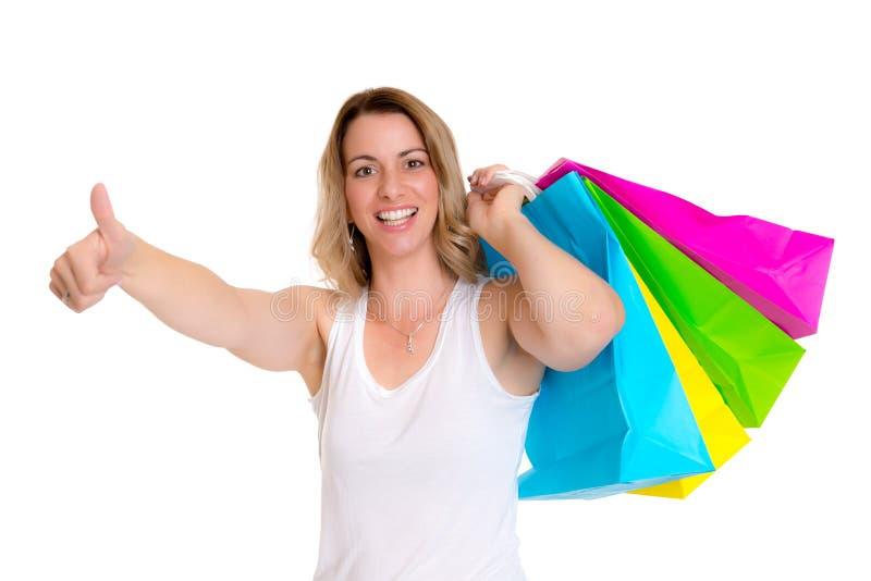 Jeune femme blonde avec les paniers et le pouce  image stock