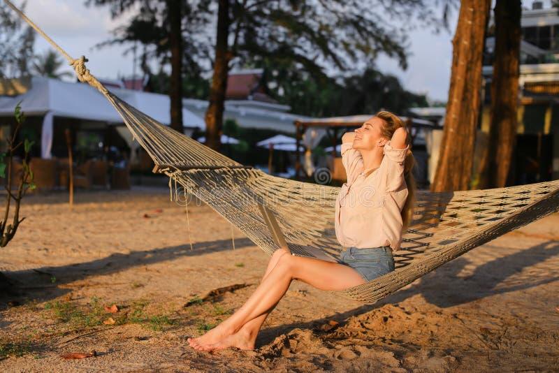 Jeune femme blonde caucasienne se reposant sur le sable dans l'hamac en osier blanc photo stock