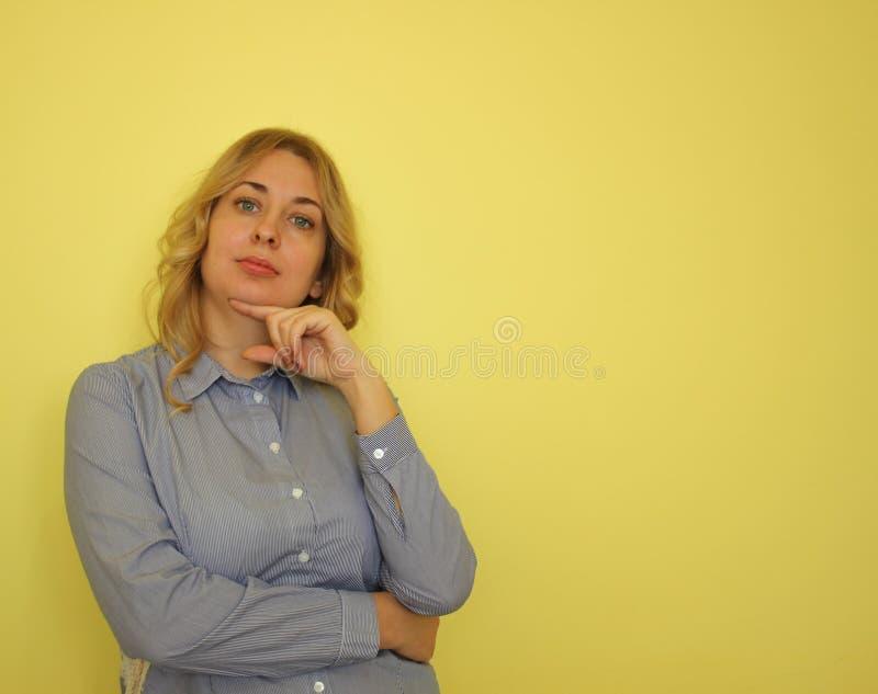 Jeune femme blonde d'affaires dans une chemise bleue sur un fond jaune photographie stock
