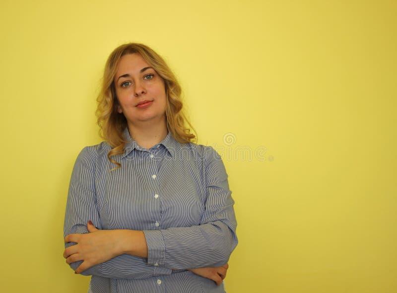Jeune femme blonde d'affaires dans une chemise bleue sur un fond jaune image stock