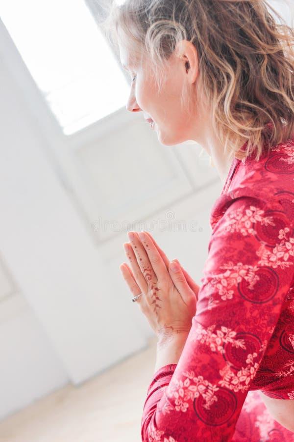 Jeune femme blonde dans l'asana de pratique rouge Namaste de yoga de costume ethnique dans le studio léger images stock