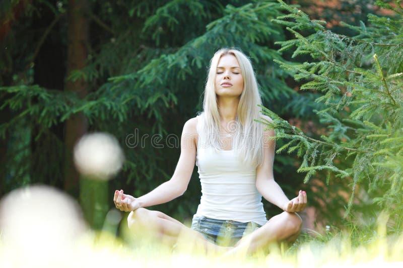 Jeune femme blonde dans la pose de lotus photo libre de droits