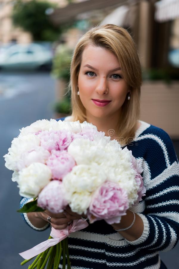 Jeune femme blonde dans la robe bleue avec le bouquet de pivoines photo stock