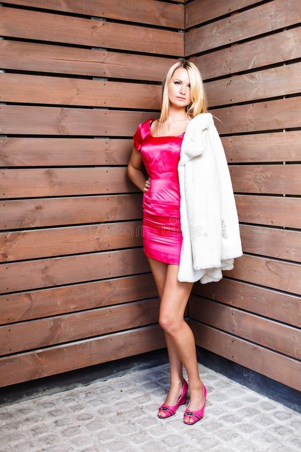 Jeune femme blonde dans la robe rose et la pose blanche de manteau image libre de droits
