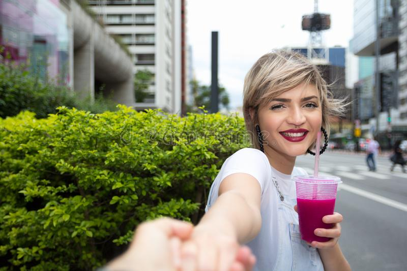Jeune femme blonde dans la ville buvant le smoothie color? photo libre de droits