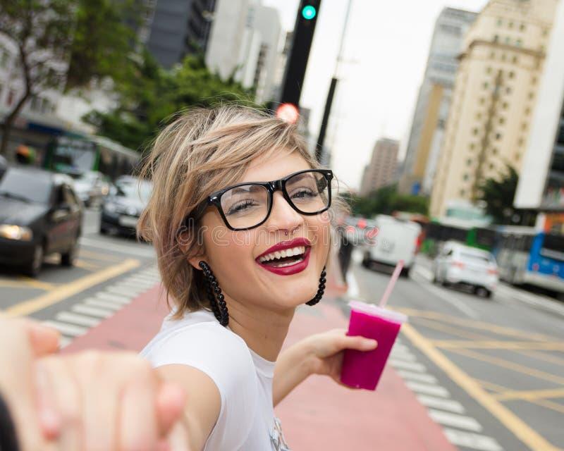 Jeune femme blonde dans la ville buvant le smoothie color? photos stock