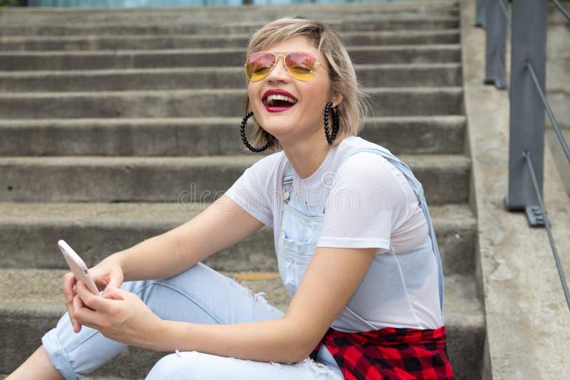 Jeune femme blonde dans la ville utilisant le t?l?phone portable photographie stock libre de droits
