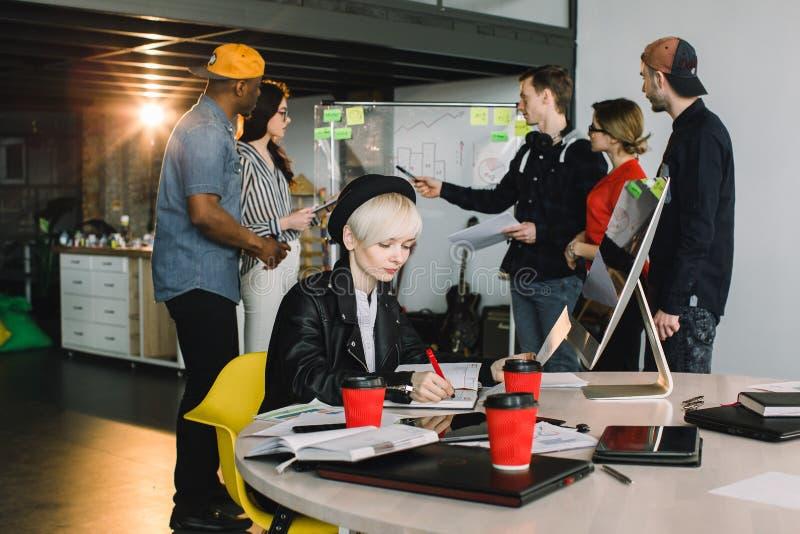 Jeune femme blonde dans le chapeau noir et la veste de loisirs se reposant à la table et fonctionnant avec des papiers Occasionne photos stock