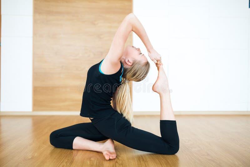 Jeune femme blonde dans un costume noir faisant le rajakapotasana de pada d'Eka d'asana de yoga de Hatha - pose unijambiste de pi photos stock