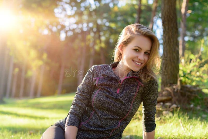 Jeune femme blonde de sourire attirante dans les vêtements de sport, détendant après séance d'entraînement image libre de droits