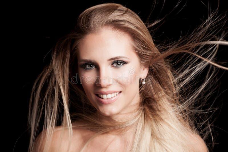 Jeune femme blonde de sourire avec de longs cheveux sains dans le mouvement images libres de droits