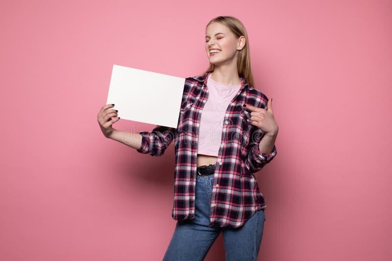 Jeune femme blonde de sourire heureuse dans des v?tements sport se tenant contre le mur rose photos stock
