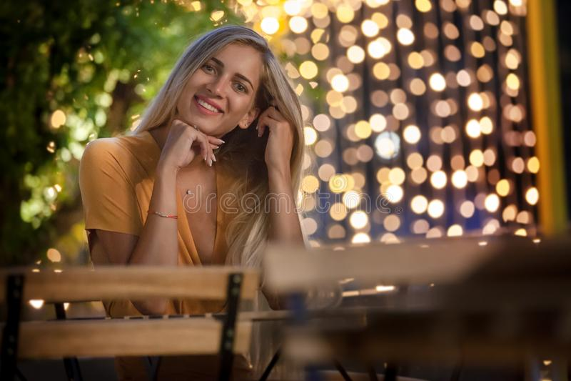 Jeune femme blonde de sourire s'asseyant, avec les quirlandes électriques de soirée sur le fond photo libre de droits