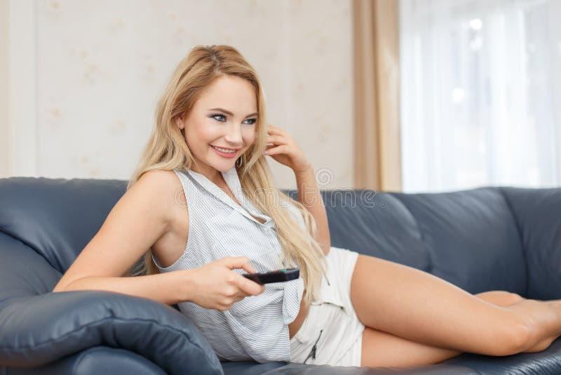 Jeune femme blonde enthousiaste regardant la TV images stock