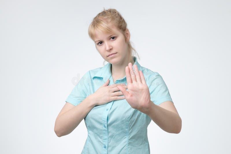 Jeune femme blonde faisant le geste d'arrêt avec sa paume photo stock