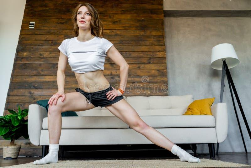 Jeune femme blonde faisant ?tirant des exercices de yoga ? la maison Style de vie sain images stock