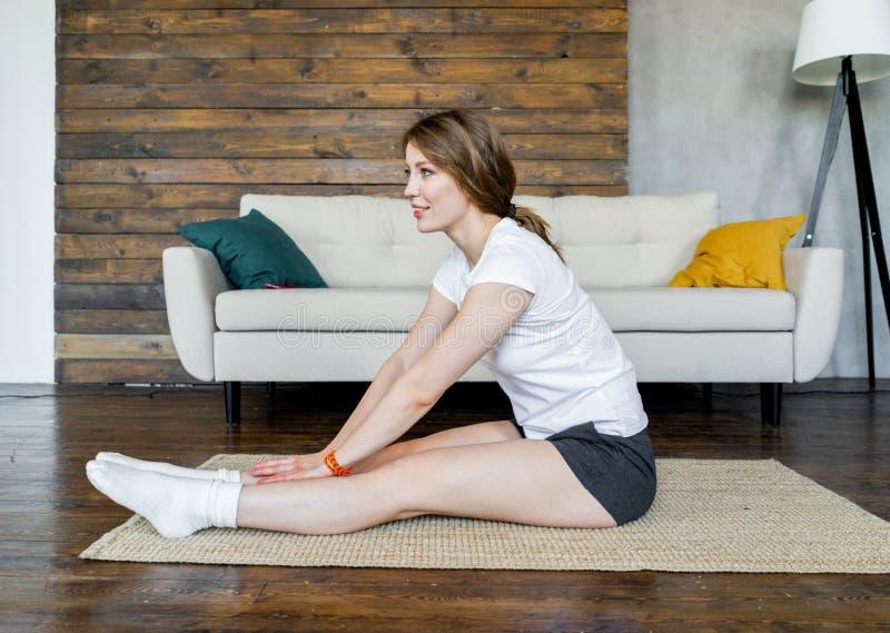 Jeune femme blonde faisant ?tirant des exercices de yoga ? la maison Style de vie sain photos stock