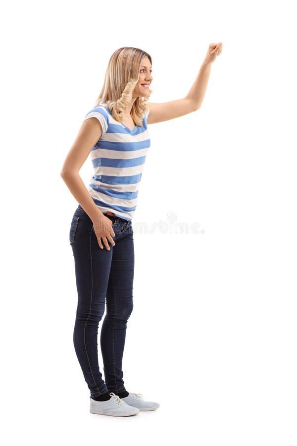 Jeune femme blonde frappant sur une porte images stock