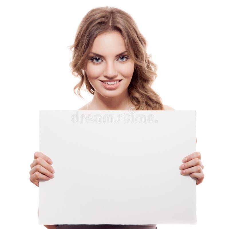 Jeune femme blonde gaie tenant un blanc blanc photo stock