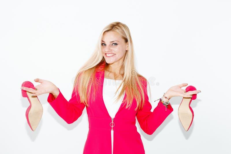 Jeune femme blonde heureuse dans l'équipement rose montrant des talons hauts photos stock