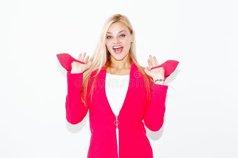 Jeune femme blonde heureuse dans l'?quipement rose tenant des talons hauts photo libre de droits